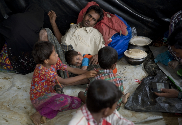 In this Saturday, Jan. 13, 2018, photo, a newly arrived Rohingya family rests together in a transit camp in the Nayaprar refugee camp near Cox's Bazar, Bangladesh. Rohingya Muslims, who have been loathed by Myanmar's Buddhist majority for decades, are locked down in their villages _ sometimes even in their homes _ and prevented from farming, fishing, foraging, trade and work. The Myanmar government denies ethnic cleansing and says it is battling terrorists. (AP Photo/Manish Swarup)