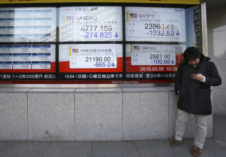 A man stands in front of electronic stock board of a securities firm in Tokyo, Friday, Feb. 9, 2018. Asian shares have opened lower and are tracking the overnight plunge on Wall Street. The Dow Jones industrial average plunged more than 1,000 points as a weeklong market swoon continued. (AP Photo/Koji Sasahara)