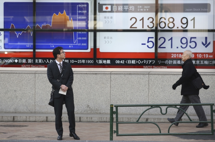 A man looks at an electronic stock board of a securities firm in Tokyo, Friday, Feb. 9, 2018. Asian shares have opened lower and are tracking the overnight plunge on Wall Street. The Dow Jones industrial average plunged more than 1,000 points as a weeklong market swoon continued. (AP Photo/Koji Sasahara)