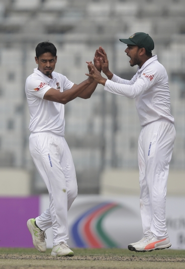 Bangladesh's Taijul Islam, left, celebrates with his teammate Mehidy Hasan Miraz the dismissal of Sri Lanka's Dhananjaya de Silva during the second day of the second and final test cricket match in Dhaka, Bangladesh, Friday, Feb. 9, 2018. (AP Photo/A.M. Ahad)