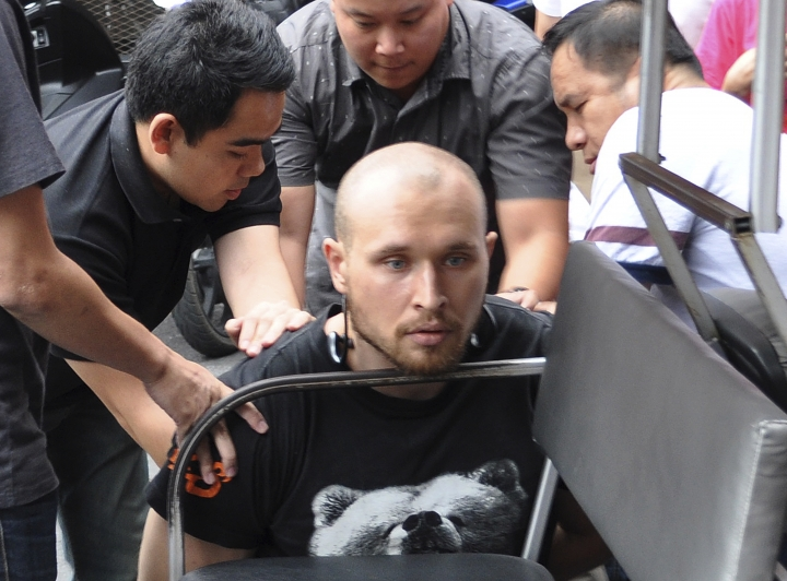 In this Friday, Feb. 2, 2018, photo released by the Crime Suppression Division of the Thailand Police, Sergey Medvedev, 31, center, is arrested outside an apartment in his role in an international identity theft ring that sold stolen credit card information on the dark web, leading to losses of over $530 million. (Crime Suppression Division of the Thailand via AP)