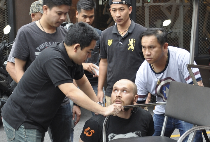 In this Friday, Feb. 2, 2018, photo released by the Crime Suppression Division of the Thailand Police, Sergey Medvedev, 31, center, is arrested outside his Bangkok apartment in his role in an international identity theft ring that sold stolen credit card information on the dark web, leading to losses of over $530 million. (Crime Suppression Division of the Thailand via AP)