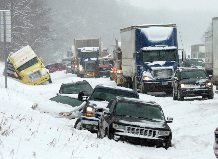 Vehicles rest along the snowbound shoulder along Interstate 94, Friday, Feb. 9, 2018, near Galesburg, Mich., after scores of vehicles were involved in an accident. (Mark Bugnaski/Kalamazoo Gazette-MLive Media Group via AP)