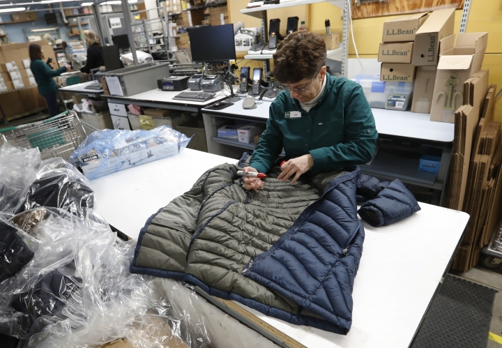 In this Friday, Feb. 2, 2018, photo a worker marks a coat that was returned to the LL Bean retail store in Freeport, Maine. L.L. Bean's generous return policy is going to be a little less forgiving: The company, which has touted its 100 percent satisfaction guarantee for more than a century, is imposing a one-year limit on most returns to reduce growing abuse and fraud. (AP Photo/Robert F. Bukaty)