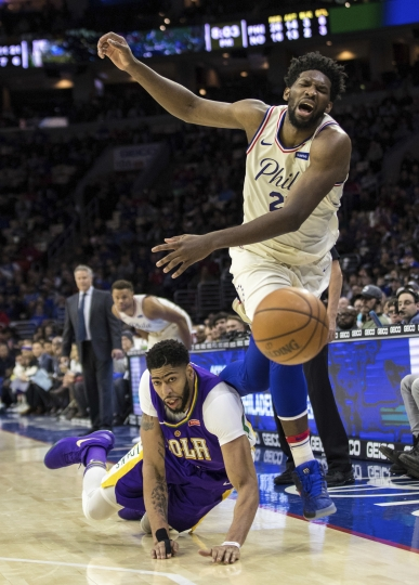 Philadelphia 76ers' Joel Embiid, right of Cameroon, tries to save the ball from going out of bounds as he collides with New Orleans Pelicans' Anthony Davis, left, during the first half of an NBA basketball game, Friday, Feb. 9, 2018, in Philadelphia. (AP Photo/Chris Szagola)