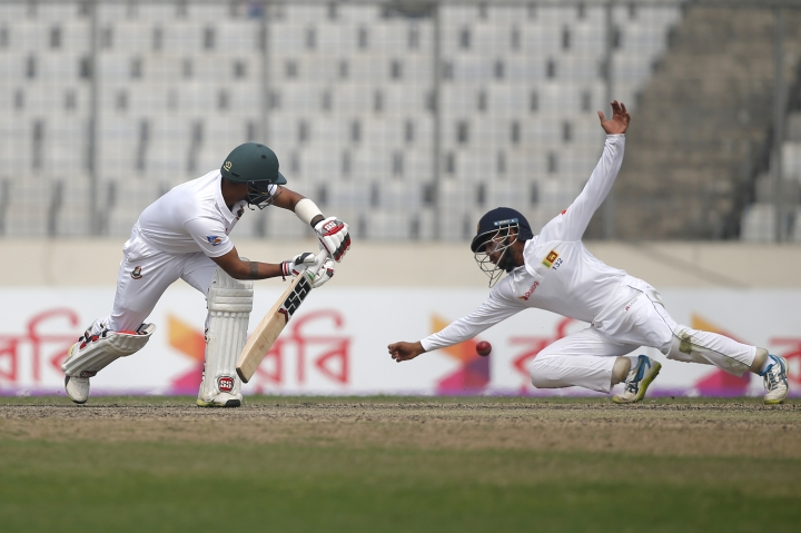 Bangladesh's captain Mahmudullah, left, plays a shot, as Sri Lanka's wKusal Mendis drives to catch the ball during the third day of the second and final test cricket match in Dhaka, Bangladesh, Saturday, Feb. 10, 2018. (AP Photo/A.M. Ahad)