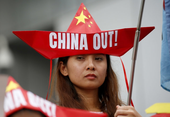 A protester, wearing boat-shaped paper hat, holds a flag during a rally at the Chinese Consulate to protest China's alleged continued militarization of the disputed islands in the South China Sea known as Spratlys Saturday, Feb. 10, 2018 in the financial district of Makati city east of Manila, Philippines. The protesters also denounced President Rodrigo Duterte's inaction over China's continued build up of military facilities and structures at the disputed islands. (AP Photo/Bullit Marquez)