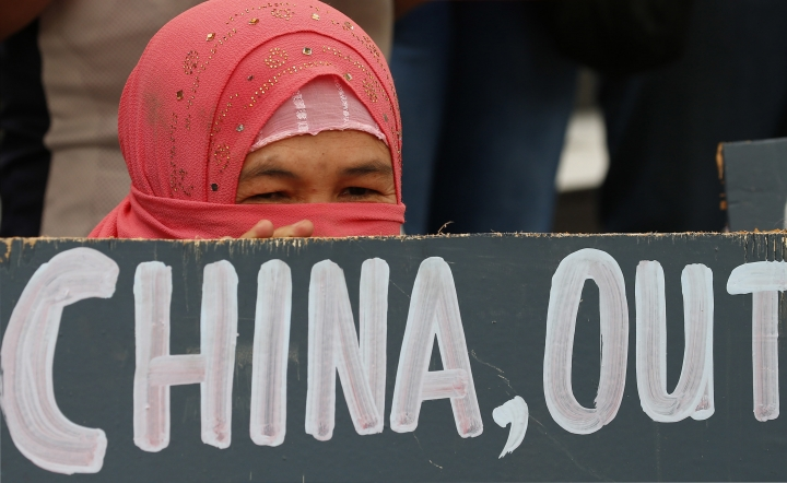 A Muslim protester displays a placard during a rally at the Chinese Consulate to protest China's alleged continued militarization of the disputed islands in the South China Sea known as Spratlys Saturday, Feb. 10, 2018, in the financial district of Makati city east of Manila, Philippines. The protesters also denounced President Rodrigo Duterte's inaction over China's continued build up of military facilities and structures at the disputed islands. (AP Photo/Bullit Marquez)