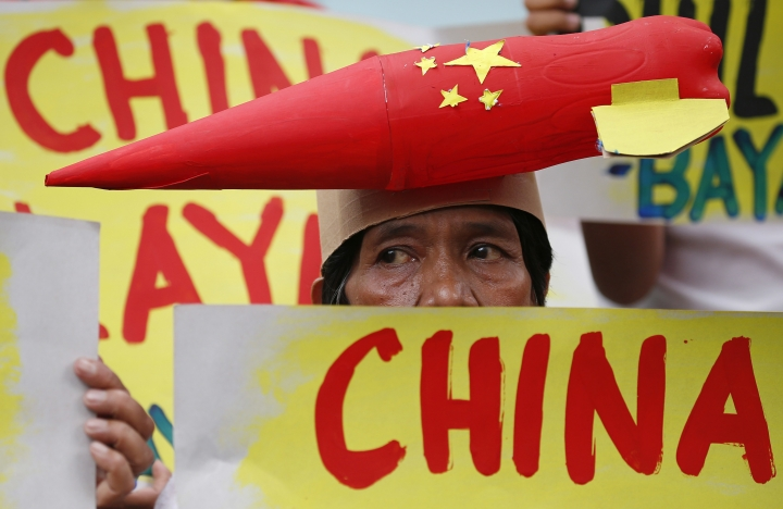 A protester wears a mock missile on her head during a rally at the Chinese Consulate to protest China's alleged continued militarization of the disputed islands in the South China Sea known as Spratlys Saturday, Feb. 10, 2018 in the financial district of Makati city east of Manila, Philippines. The protesters also denounced President Rodrigo Duterte's inaction over China's continued build up of military facilities and structures at the disputed islands. (AP Photo/Bullit Marquez)