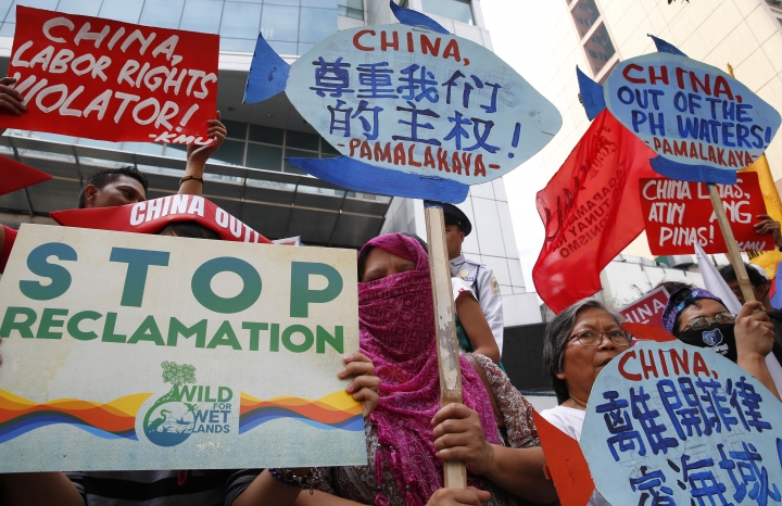 Protesters display placards during a rally at the Chinese Consulate to protest China's alleged continued militarization of the disputed islands in the South China Sea known as Spratlys Saturday, Feb. 10, 2018 in the financial district of Makati city east of Manila, Philippines. The protesters also denounced President Rodrigo Duterte's inaction over China's continued build up of military facilities and structures at the disputed islands. (AP Photo/Bullit Marquez)