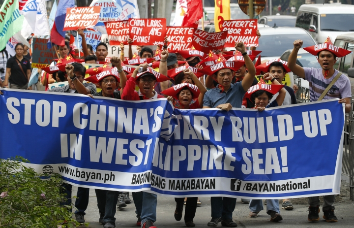 Protesters, wearing boat-shaped paper hats, shout slogans as they march for rally at the Chinese Consulate to protest China's alleged continued militarization of the disputed islands in the South China Sea known as Spratlys Saturday, Feb. 10, 2018 in the financial district of Makati city east of Manila, Philippines. The protesters also denounced President Rodrigo Duterte's inaction over China's continued build up of military facilities and structures at the disputed islands. (AP Photo/Bullit Marquez)