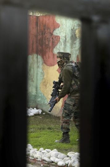 An Indian Army soldier takes guard at the Sunjwan Army camp in Jammu, India, Saturday, Feb. 10, 2018. A group of militants in Indian Kashmir opened fire Saturday inside an army camp in the disputed region, police said. The attack began early in the morning and it was unclear how many gunmen were involved. (AP Photo/Channi Anand)