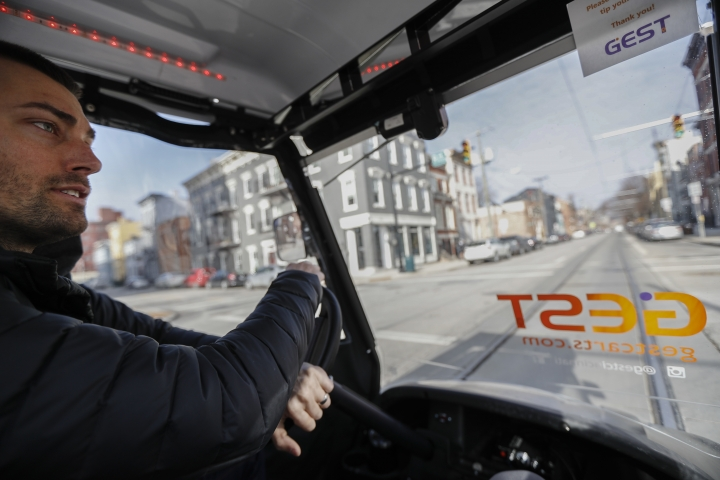 Patrick Dye, co-founder of GEST Carts, drives through the downtown as he demonstrates his retrofitted golf carts Thursday, Jan. 25, 2018, in Cincinnati. GEST Carts offers rides on weekend nights to attractions such as riverfront restaurants, a casino and other entertainment spots. Patrick and Lauren Dye have rolled out the service slowly, with plans to expand in time for Cincinnati's popular Opening Day festivities in late March when the Reds begin baseball season. (AP Photo/John Minchillo)