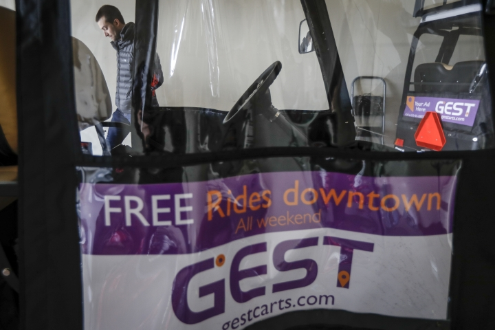 Patrick Dye, co-founder of GEST Carts, stands beside his retrofitted golf carts at their depot, Thursday, Jan. 25, 2018, in Cincinnati. GEST Carts offers rides on weekend nights to attractions such as riverfront restaurants, a casino and other entertainment spots. Patrick and Lauren Dye have rolled out the service slowly, with plans to expand in time for Cincinnati's popular Opening Day festivities in late March when the Reds begin baseball season. (AP Photo/John Minchillo)