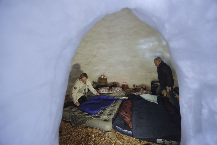 In this photo taken on Friday, Feb. 2, 2018, tourists Elena Rota and Giovanni di Giovanni prepare beds for the night inside an igloo, at an igloo village in San Simone di Valleve, near Bergamo, northern Italy. The local hotel now houses about 80 African asylum-seekers who were assigned to live there, but those migrants have picked up the art of igloo making to help a local restaurant owner realize a project to lure tourists back to this dying mountain resort. (AP Photo/Luca Bruno)