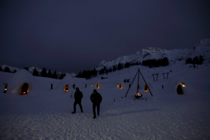 In this photo taken on Friday, Feb. 2, 2018, tourists walk after sunset in an igloo village in San Simone di Valleve, near Bergamo, northern Italy. With this year's significant snowfall, restaurant owner Davide Midali, with the help of migrants from Africa, set out to create a series of igloos to house guests overnight in what once was a thriving ski resort. (AP Photo/Luca Bruno)