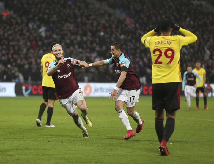 West Ham United's Marko Arnautovic, left, celebrates scoring the second goal of the game during the English Premier League soccer match between West Ham United and Watford at the London Stadium, London, England. Saturday Feb. 10, 2018. (Steven Paston/PA via AP)