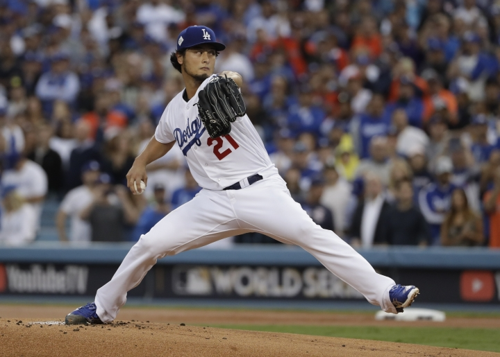 FILE - In this Nov. 1, 2017, file photo, Los Angeles Dodgers starting pitcher Yu Darvish throws during the first inning of Game 7 of baseball's World Series against the Houston Astros, in Los Angeles. Perhaps 100 free agents still seek contracts as the start of spring training workouts on Feb. 14 draws near, a group that includes J.D. Martinez, Eric Hosmer, Mike Moustakas, Jake Arrieta and Yu Darvish. (AP Photo/Matt Slocum, File)