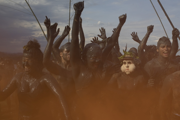 """People covered in mud dance amid orange smoke in the traditional """"Bloco da Lama"""" or """"Mud Block"""" carnival party in Paraty, Brazil, Saturday, Feb. 10, 2018. Hundreds of revelers wrestled, tackled each other and threw chunks of gunk Saturday while shaking it to samba and reggaeton at a Carnival beach party where clothes were optional but the mud was not. (AP Photo/Leo Correa)"""