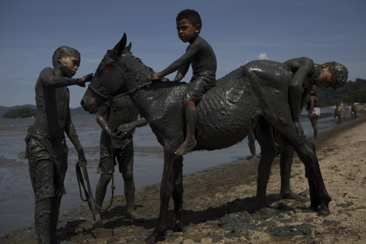 "Kids cover a horse with mud as they take part in the traditional ""Bloco da Lama"" or ""Mud Block"" carnival party in Paraty, Brazil, Saturday, Feb. 10, 2018. Hundreds of revelers wrestled, tackled each other and threw chunks of gunk Saturday while shaking it to samba and reggaeton at a Carnival beach party where clothes were optional but the mud was not. (AP Photo/Leo Correa)"