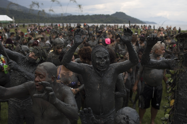 """People covered in mud take part in the traditional """"Bloco da Lama"""" or """"Mud Block"""" carnival party in Paraty, Brazil, Saturday, Feb. 10, 2018. Hundreds of revelers wrestled, tackled each other and threw chunks of gunk Saturday while shaking it to samba and reggaeton at a Carnival beach party where clothes were optional but the mud was not. (AP Photo/Leo Correa)"""