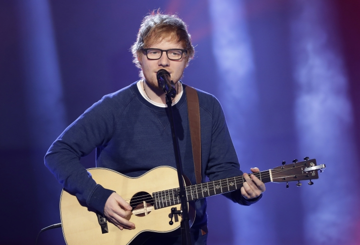"""FILE - In this file photo dated Sunday, March 12, 2017, British singer Ed Sheeran performs during the Italian State RAI TV program """"Che Tempo che Fa"""", in Milan, Italy. Sheeran is reported to be friends with some of the younger royals and may be asked to perform during the May 19, 2018, royal wedding of Prince Harry and Meghan Markle. (AP Photo/Antonio Calanni, FILE)"""