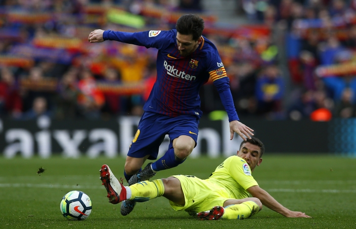 FC Barcelona's Lionel Messi, top, duels for the ball against Getafe's Mathieu Flamini during the Spanish La Liga soccer match between FC Barcelona and Getafe at the Camp Nou stadium in Barcelona, Spain, Sunday, Feb. 11, 2018. (AP Photo/Manu Fernandez)