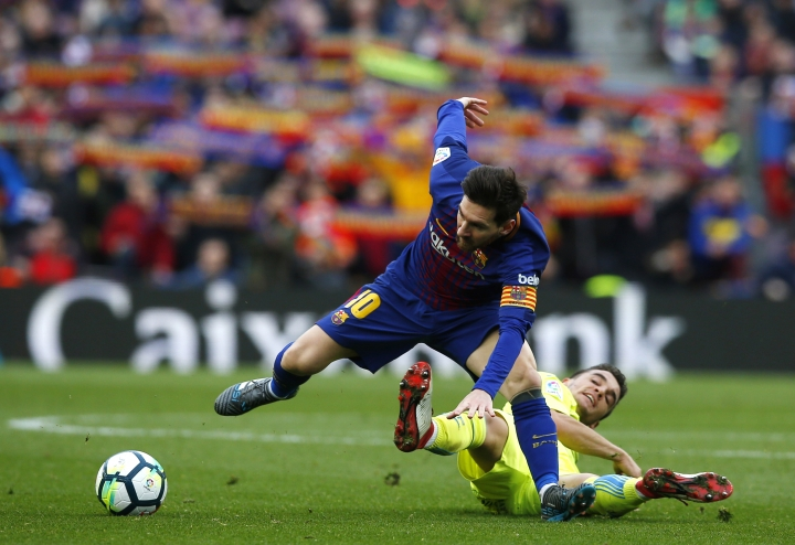 FC Barcelona's Lionel Messi, left, duels for the ball against Getafe's Mauro Arambarri during the Spanish La Liga soccer match between FC Barcelona and Getafe at the Camp Nou stadium in Barcelona, Spain, Sunday, Feb. 11, 2018. (AP Photo/Manu Fernandez)