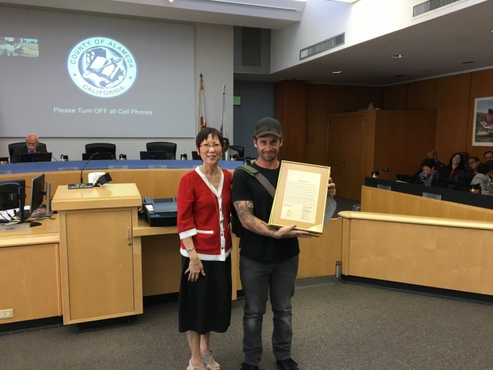 This photo provided by Alameda County, shows Alameda County Supervisor Wilma Chan presenting a Cliff Burton Day proclamation to Robert Souza, who led a petition drive that led to the board's declaration. Supervisors in Alameda County named Feb. 10 Cliff Burton Day, in honor of the late bassist of Metallica who was born in Castro Valley south of Oakland. Burton was 24 when he was killed in a bus accident in 1986. He would've turned 56 on Saturday. (Courtesy of Alameda County)