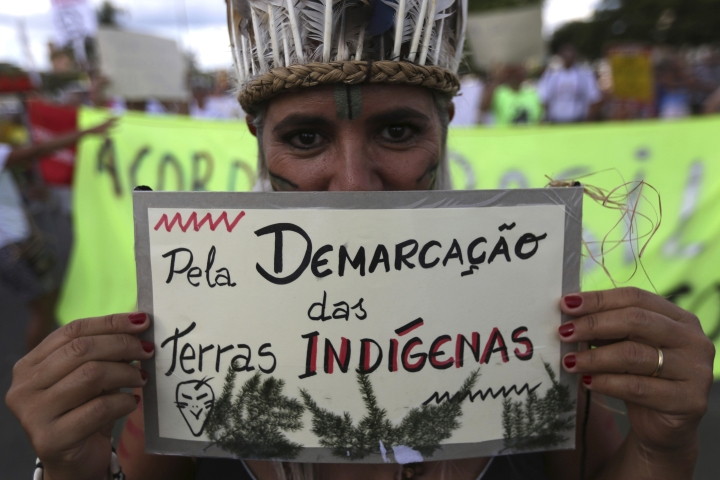"An reveler in indigenous costume holds a sign that reads in Portuguese ""For the demarcation of indigenous lands"" during the Pacotao street carnival in Brasilia, Brazil, Sunday, Feb. 11, 2018. The Pacotao parade theme this year is The Mad President. (AP Photo/Eraldo Peres)"