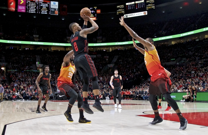 Portland Trail Blazers guard Damian Lillard, center, shoots over Utah Jazz forward Jae Crowder, left, and forward Derrick Favors, right, during the first half of an NBA basketball game in Portland, Ore., Sunday, Feb. 11, 2018. (AP Photo/Craig Mitchelldyer)