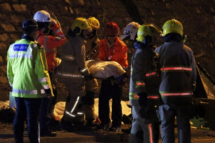Rescuers carry a body after a bus crashed in Hong Kong, China February 10, 2018.  REUTERS/Bobby Yip