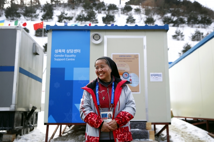 In this Feb. 12, 2018 photo, Sungsook Kim, a Catholic nun who goes by her religious name, Sister Droste, poses for a photograph outside her trailer office, the Gender Equality Support Centre, at Phoenix Snow Park during the 2018 Winter Olympics in Pyeongchang, South Korea. For the first time at the Olympics, there is an organized and advertised contingent of offices designed to help sexual assault victims dotted around the Games' sprawling venues. (AP Photo/Patrick Semansky)