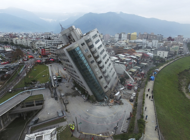 FILE - In this Feb. 7, 2018, file photo, a residential building leans on a collapsed first floor following an earthquake, in Hualien, southern Taiwan. A memorial service is being held on Monday, Feb. 12, 2018, for the 17 people who died after the strong earthquake hit Taiwan's east coast last week. Members of the military and police force, religious group volunteers and city workers paid their respects before a row of the victims' framed photographs. (Central News Agency via AP, File)