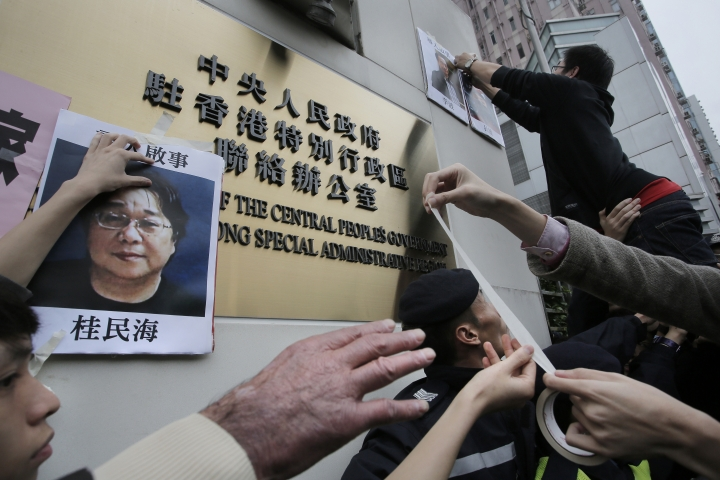 "FILE - In this Jan. 3, 2016, file photo, protesters try to stick photos of missing booksellers, one of which shows Gui Minhai at left, during a protest outside the Liaison of the Central People's Government in Hong Kong. Gui Minhai, a Hong Kong-based publisher who sold books of gossip about Chinese leaders, told several outlets including the South China Morning Post that he never wanted to leave China and that Stockholm was using his case to ""create trouble."" (AP Photo/Vincent Yu, File)"