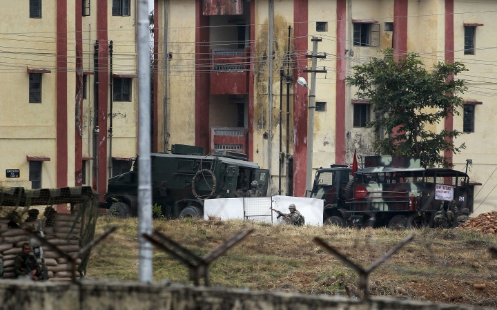 An Indian Army soldier takes position after surrounding the residential quarters where militants are believed to be holed up in an Army camp in Jammu, India, Sunday, Feb.11, 2018. At least two soldiers were killed and three others wounded in Indian-controlled Kashmir on Saturday as soldiers traded fire with armed militants who were holed up inside an army camp, officials said. (AP Photo/Channi Anand)