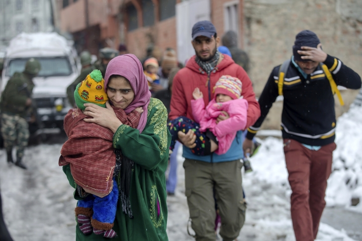Kashmiri people flee from the site of a gunbattle between paramilitary force soldiers and armed militants in Srinagar, Indian controlled Kashmir, Monday, Feb. 12, 2018. Two gunmen have opened fire near a paramilitary camp in the main city of Indian controlled Kashmir killing at least one soldier. The attack comes hours after government troops ended a two day gunbattle with three armed gunmen at an army camp in another part of the disputed region. (AP Photo/Dar Yasin)