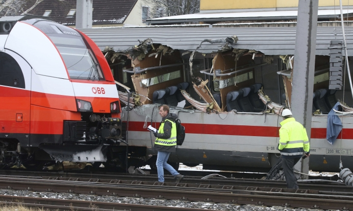 Rescuers and rail workers walk at the scene of a train crash in Niklasdorf, Austria, Monday, Feb. 12, 2018. Two passenger trains collided near a station of Niklasdorf. Two passenger trains crashed in central Austria on Monday, killing one person and injuring more than 20 others, authorities said. One train hit the side of the other near the station in Niklasdorf, a town 60 kilometers (40 miles) north of Graz, said Graz police spokesman Leo Josefus. (AP Photo/Ronald Zak)