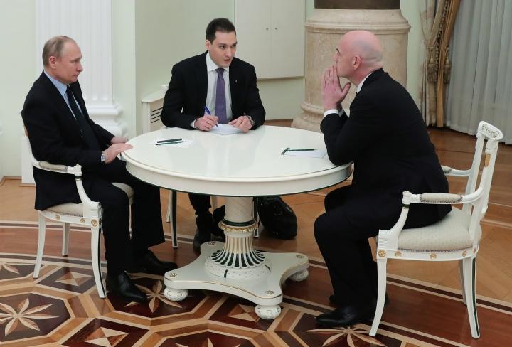 Russian President Vladimir Putin, left, speaks to FIFA president Gianni Infantino, right, during their meeting in the Kremlin in Moscow, Russia, Monday, Feb. 12, 2018. (Mikhail Klimentyev/Pool Photo via AP)