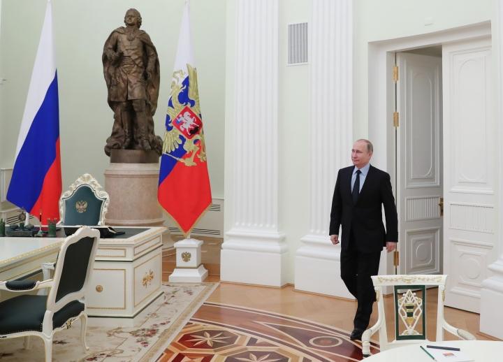Russian President Vladimir Putin enters a hall to meet FIFA president Gianni Infantino in the Kremlin in Moscow, Russia, Monday, Feb. 12, 2018. (Mikhail Klimentyev/Pool Photo via AP)