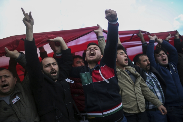 People shout slogans in support of Turkish soldiers during the funeral of Ali Akdogan in Izmir, Turkey, Sunday, Feb. 11, 2018. Akdogan was one of 12 Turkish soldiers killed Saturday during Turkey's Operation Olive Branch against the Syrian Kurdish militia that started on Jan. 20 with Ankara's cross-border incursion into the enclave of Afrin, Syria.(AP Photo/Emre Tazegul)