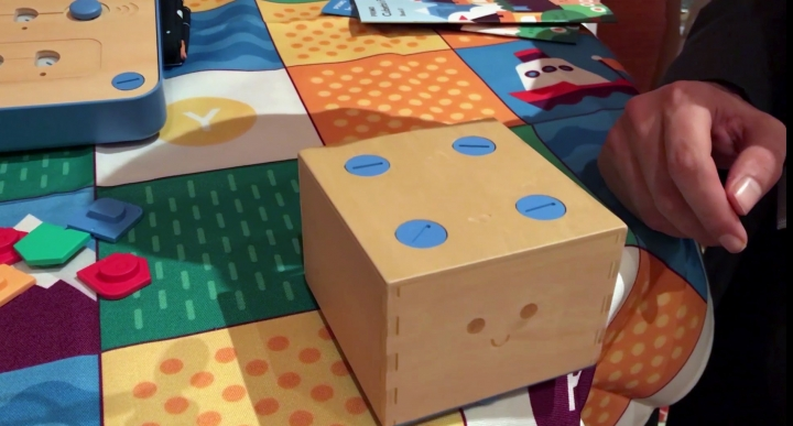 """In this Jan. 9, 2018, image made from a video, the Cubetto robot moves across a table following commands input into a board using blocks at the CES gadget show in Las Vegas. The """"Cubetto"""" block on wheels responds to where chip-embedded pieces are put on a wooden board. Different colors represent different commands, for example, to """"go straight"""" or """"turn left."""" (AP Photo/Ryan Nakashima)"""