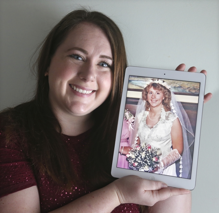 Ame Bartlebaugh holds a 1980 photo of her mother in her wedding dress in Willowick, Ohio. Bartlebaugh posted pictures on Facebook of a lacy wedding dress, a veil and a hoop skirt with an explanation of a1985 mix-up with the now-defunct, dry cleaner who gave her the dress, thinking it was her mothers. Bartlebaugh found the rightful owner of the dress but is still searching for her mothers dress that she hopes to wear at her wedding in December 2019. (Phil Masturzo/Akron Beacon Journal via AP)