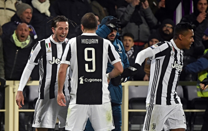 Juventus' Federico Bernardeschi, left, celebrates with teammate Gonzalo Higuain after scoring during a Serie A soccer match between Fiorentina and Juventus at the Artemio Franchi stadium in Florence, Italy, Friday, Feb. 9, 2018. (Maurizio Degl'Innocenti/ANSA via AP)