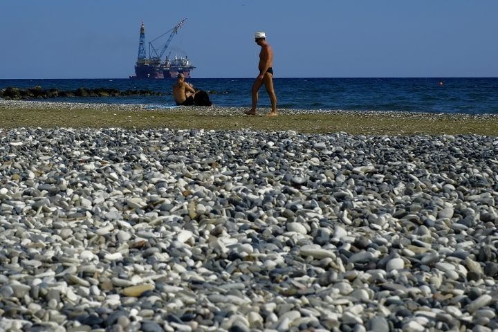 FILE - In this Sunday, Oct. 15, 2017 file photo, a man walks as an other man sits on a beach during a warm day as a drilling platform is seen in the background, outside from Larnaca port, in the eastern Mediterranean island of Cyprus. Turkish warships continue to impede a rig from reaching a location off Cyprus where Italian energy company Eni is scheduled to drill for gas, the Cypriot government said Monday, Feb. 12, 2018. (AP Photo/Petros Karadjias, File)
