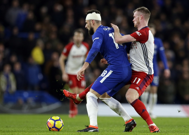 Chelsea's Oliver Giroud, left, holds off the challenge of West Bromwich Albion's Chris Brunt during the English Premier League soccer match between Chelsea and West Bromwich Albion at Stamford Bridge stadium in London, Monday, Feb. 12, 2018. (AP Photo/Alastair Grant)