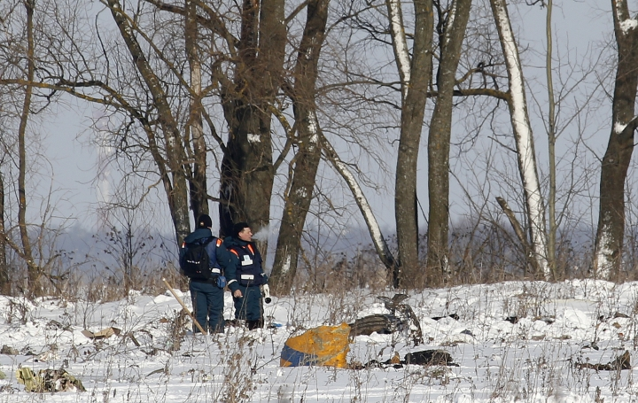 Personnel stand near the scene of a AN-148 plane crash in Stepanovskoye village, about 40 kilometers (25 miles) from the Domodedovo airport, Russia, Monday, Feb. 12, 2018. A Russian passenger plane carrying 71 people crashed Sunday near Moscow, killing everyone aboard shortly after the jet took off from one of the city's airports. The Saratov Airlines regional jet disappeared from radar screens a few minutes after departing from Domodedovo Airport en route to Orsk, a city some 1,500 kilometers (1,000 miles) southeast of Moscow. (AP Photo/Alexander Zemlianichenko)