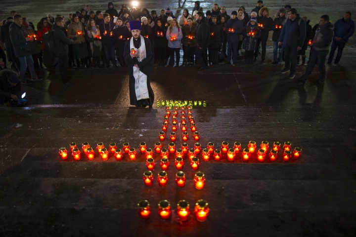 Orthodox youth with a priest gather at the Cathedral of Christ the Saviour in Moscow lighting 71 candles in memory of those killed in Sunday's An-148 plane crash, Monday, Feb. 12, 2018. A Russian passenger plane carrying 71 people crashed Sunday near Moscow, killing everyone aboard shortly after the jet took off from one of the city's airports. The Saratov Airlines regional jet disappeared from radar screens a few minutes after departing from Domodedovo Airport en route to Orsk, a city some 1,500 kilometers (1,000 miles) southeast of Moscow. (AP Photo/Alexander Zemlianichenko)