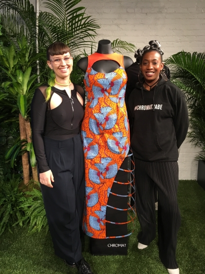 "Becca McCharen-Tran, left, the founder of Chromat, stands with Chromat designer Tolu Aremu and a dress they created for a small collection inspired by the film ""Black Panther,"" Monday, Feb. 12, 2018 in New York. The collection will be auctioned to benefit the nonprofit Save the Children. (AP Photo/Leanne Italie)"