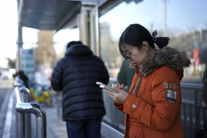 "In this Feb. 7, 2018 photo, Jia Weiwei plays the Japanese mobile game Travel Frog on her smartphone at a bus stop in Beijing. The Japanese mobile game Travel Frog has attracted a massive following in China by speaking to a desire for a more passive existence among harried youngsters that some have termed ""Buddhist style"" for its desired goal of Zen-like serenity. (AP Photo/Dake Kang)"